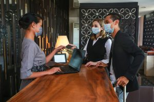 Couple,And,Receptionist,At,Counter,In,Hotel,Wearing,Medical,Masks